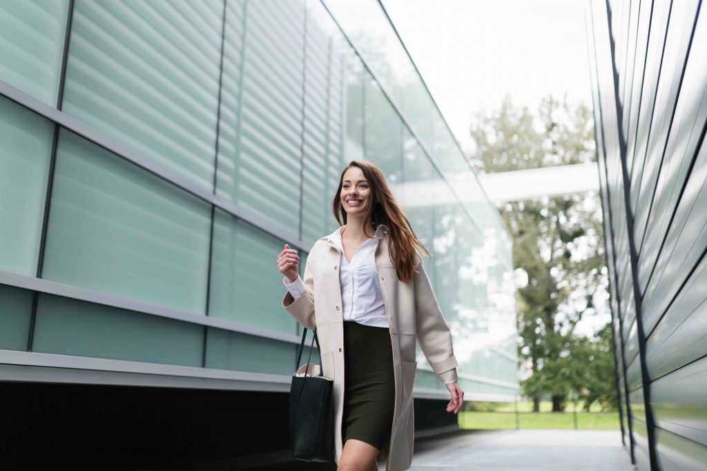 Portrait of young successful beautiful businesswoman going to office